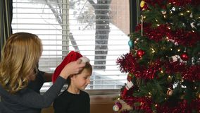 Child hangs candy cane on tree stock video footage