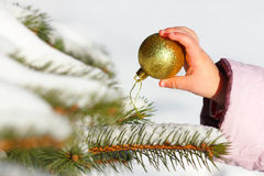 child hangs the ball on the Christmas tree Royalty Free Stock Photo