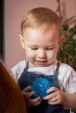 Child happily holding a toy in the hands of. The child got a new toy Royalty Free Stock Photography