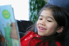 Child happily reading a book Royalty Free Stock Images