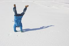Child happiness. Somersault on the snow under the blue sky Royalty Free Stock Image