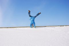 Child happiness. Somersault on the snow under the blue sky Royalty Free Stock Images