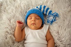 Child, happiness and childhood concept - beautiful sleeping baby in blue hat stock image