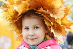 Child happy face with yellow maples Royalty Free Stock Images