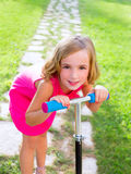 Child happy girl playing with scooter in garden Stock Images