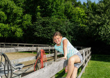 Child happy joyful girl sitting on wooden fence in park Stock Images