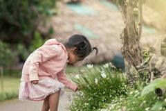 Child happy little girl  having fun with  flower in the garden Stock Photos