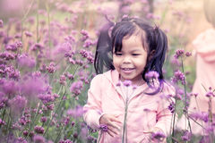 Child happy little girl  running and having fun in flower field Stock Photo