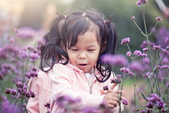 Child happy little girl  running and having fun in flower field Royalty Free Stock Photos