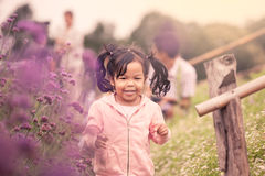 Child happy little girl  running and having fun in flower field Stock Image