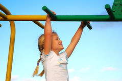 Child happy playground. A cute little caucasian girl child with happy smiling facial expression having great fun by hanging on a jungle gym on the playground in Stock Photography