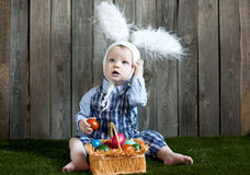 Child in a hare costume with a basket of colorful eggs Royalty Free Stock Images