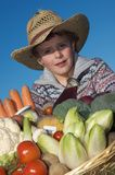 Child with harvest vegetables. Boy (7) dressed as a farmer, with a large basket with vegetables against a clear blue sky Royalty Free Stock Photo