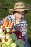 Child with harvest vegetables. Boy (7) dressed as a farmer, holding a large basket with vegetables Stock Photography