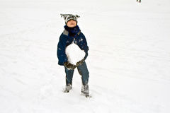 Child has a big snowball for Royalty Free Stock Image