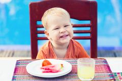 Child has a breakfast. Near a swimming pool Royalty Free Stock Photo