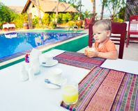 Child has a breakfast. Near a swimming pool Royalty Free Stock Images