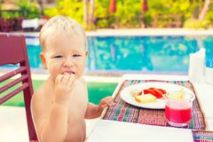 Child has a breakfast. Near a swimming pool Royalty Free Stock Photos