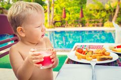 Child has a breakfast. Near a swimming pool Stock Photo