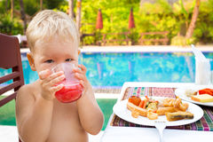 Child has a breakfast. Near a swimming pool Stock Photography