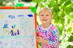 The child has drawn the drawing of family. On a board in the park stock photos