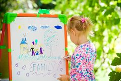 The child has drawn the drawing of family. On a board in the park stock images