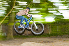 Child has fun jumping with the bike over a ramp. In open area Stock Photo