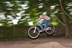 Child has fun jumping with the bike over a ramp. In open area Royalty Free Stock Photos