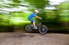 Child has fun jumping with the bike over a ramp. In open area Royalty Free Stock Photography
