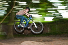 Child has fun jumping with the bike over a ramp. In open area Stock Photos