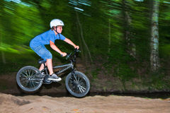 Child has fun jumping with thé bike. Over a ramp in open area Stock Image