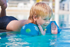 Child has fun in the swimming-pool. Happy kid is playing in the pool Stock Photos