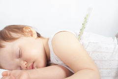 Child has a high temperature or fever, using a thermometer Royalty Free Stock Image
