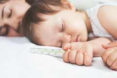 Child has a high temperature or fever, using a thermometer Royalty Free Stock Images