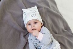 Child has his finger in his mouth. Baby girl in cute hat stock photography