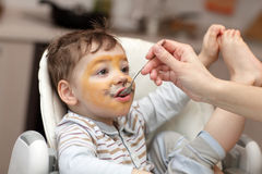 Child has lunch. Child with painted tiger face has lunch royalty free stock photography