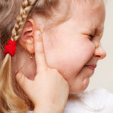 Child has a sore ear. Little girl suffering from otitis Stock Photography