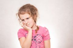 Child has a sore ear. Little girl suffering from otitis. Young girl has a toothache, facial expression concept royalty free stock photo