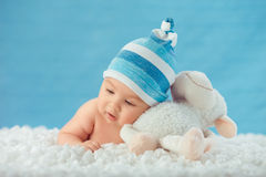 Child in hat hugging toy on a white bedspread Stock Photo