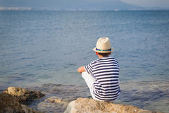 Child in hat looking at sea and ship Stock Photos