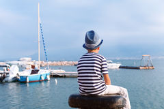 Child in hat looking at sea and ship Stock Images