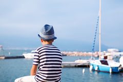 Child in hat looking at sea and ship Stock Photography
