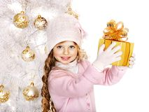 Child in hat and mittens holding Christmas  gift box. Royalty Free Stock Image