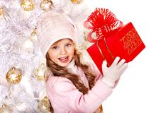Child in hat and mittens holding red gift box . Child in hat and mittens holding red gift box near white Christmas tree. Isolated royalty free stock photo