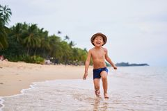 A child in a hat runs and smiles - Asian boy in a hat, blurred background royalty free stock photo