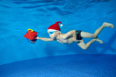 Child in hat Santa Claus swims underwater with a gift in hand on blue background. The view from under the water. Horizontal orientation Royalty Free Stock Photo