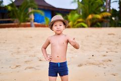 A child in a hat is standing on the sandy beach of the ocean stock photo