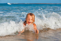 Child have a fun in breaking beach waves Royalty Free Stock Photo