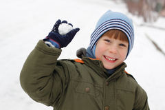 Child have fun with snowball fight. Winter outdoor stock photo