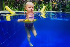 Child have a swimming lesson on polyfoam noodle in pool Stock Images